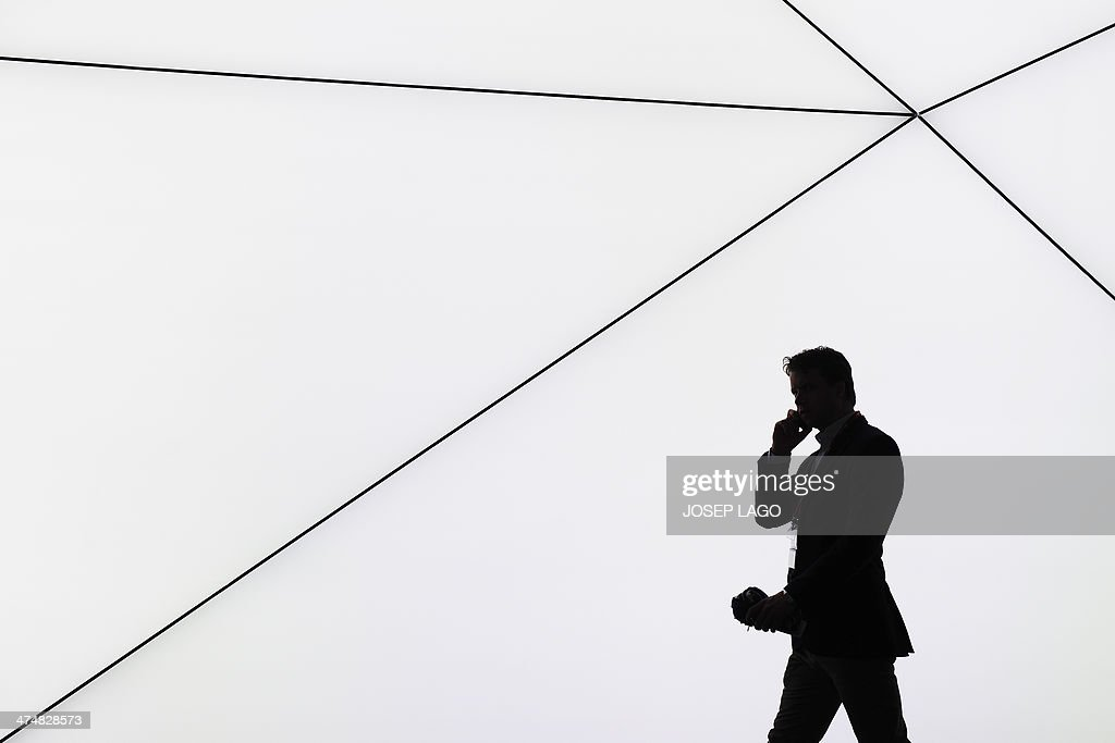 A visitor speaks on his phone in Barcelona on February 25 2014 during the second day of the 2013 Mobile World Congress The 2014 Mobile World Congress...