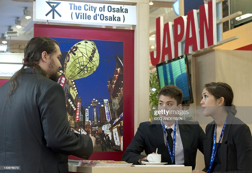 A visitor speaks with representatives of Japan's travel industry at the ITB international tourism fair in Berlin on March 9, 2012 . The ITB travel trade show, with 10,644 exhibitors from 187 countries, is due to run until March 11.