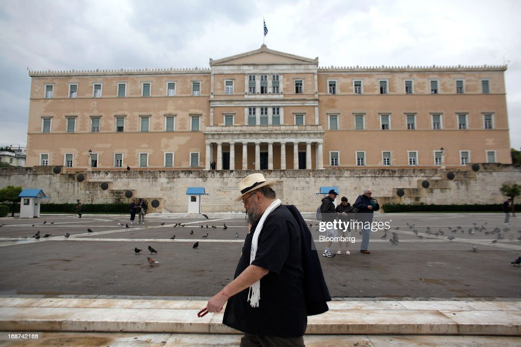 Visitor stand in front of the Greek parliament on Syntagma square in central Athens, Greece, on Tuesday, May 14, 2013. Greek Prime Minister Antonis Samaras said the country can beat the targets set under its 240 billion-euro ($311 billion) International Monetary Fund and euro area bailout program and return to bond markets in the first half of next year. Photographer: Kostas Tsironis/Bloomberg via Getty Images