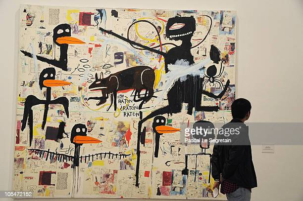 A visitor stands among paintings by artist JeanMichel Basquiat which are part of an exhibition of 150 works of art by Basquiat shown at Musee d'Art...