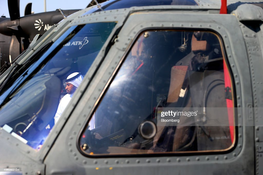 A visitor stands beside a Black Hawk UH60 military helicopter manufactured by Sikorsky Aircraft Corp on the second day of the 14th Dubai Air Show at...
