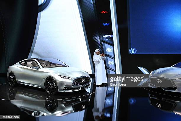 A visitor stands beside an Infiniti Q60 Concept vehicle left while photographing an Infiniti Q80 Inspiration automobile manufactured by Infiniti...