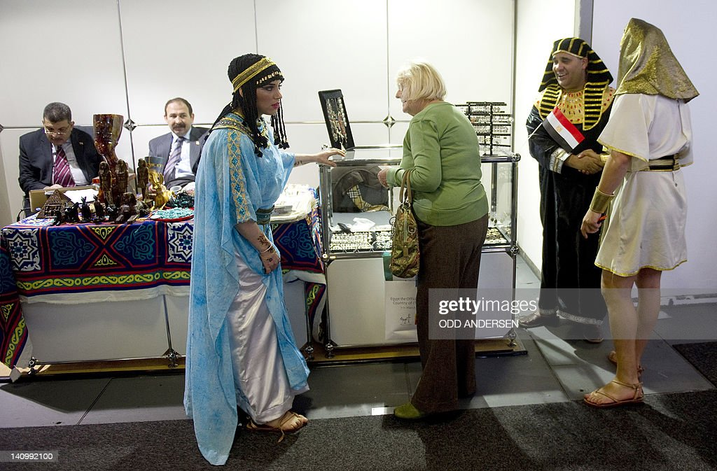 A visitor stands by dressed representatives of Egypt's travel industry on their booth at the ITB international tourism fair at the fairgrounds in...