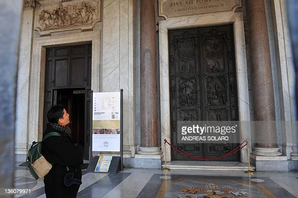 A visitor stands by the entrance door of the papal basilica of Santa Maria Maggiore after a vandal attacked the bronze and wooden door with a stone...