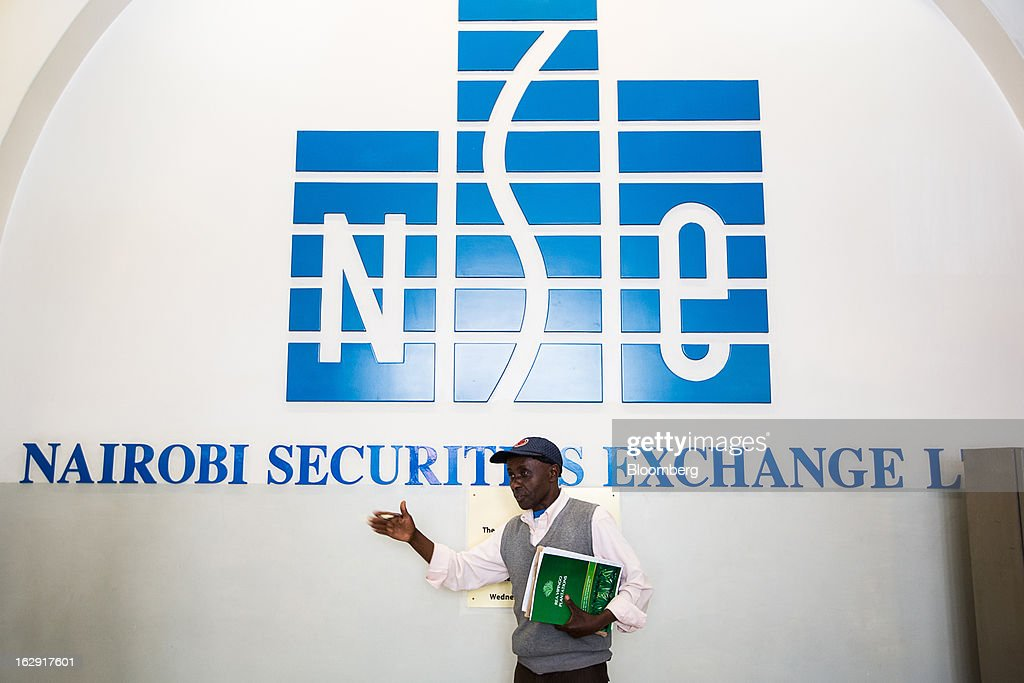 A visitor stands in front of a logo inside the Nairobi Stock Exchange (NSE) in Nairobi, Kenya, on Friday, March 1, 2013. Next week's presidential vote will be the first since disputed elections in 2007 triggered ethnic fighting in which more than 1,100 people died and another 350,000 fled their homes. Photographer: Trevor Snapp/Bloomberg via Getty Images