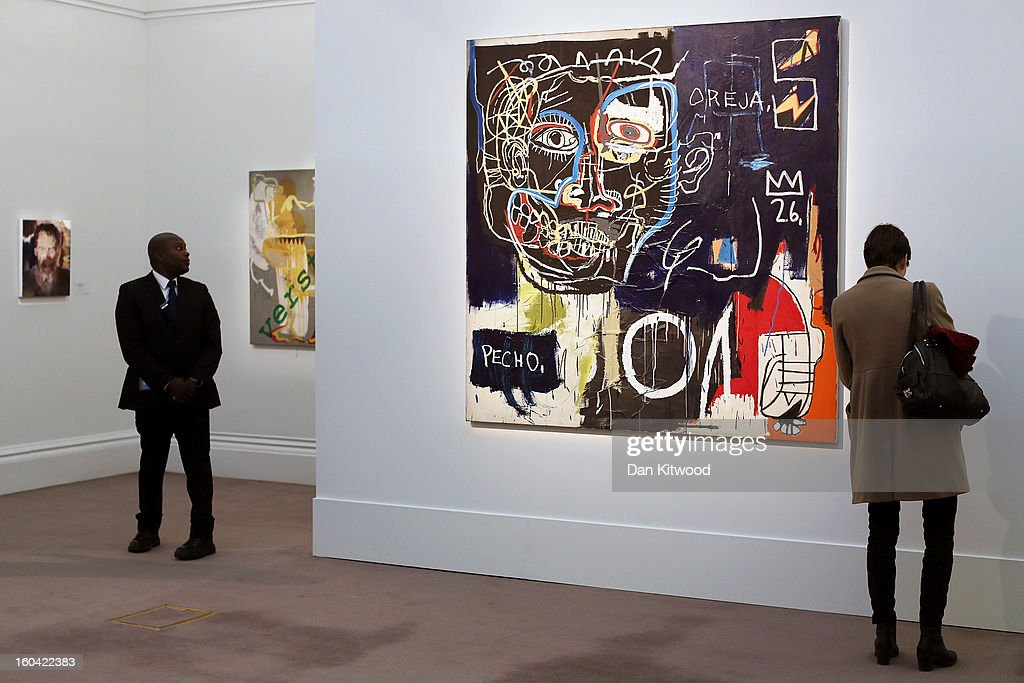 A visitor stands in front of a painting by Jean-Michel Basquiat entitled 'Untitled,' on January 31, 2013 in London, England. The piece makes up a selection of works by artists including Monet, Miro, Picasso and Richter and is estimated to sell for between 7-9 Million GBP at auction in the 'Contemprary Art' evening sale at Sotheby's auction house on February 12, 2013.