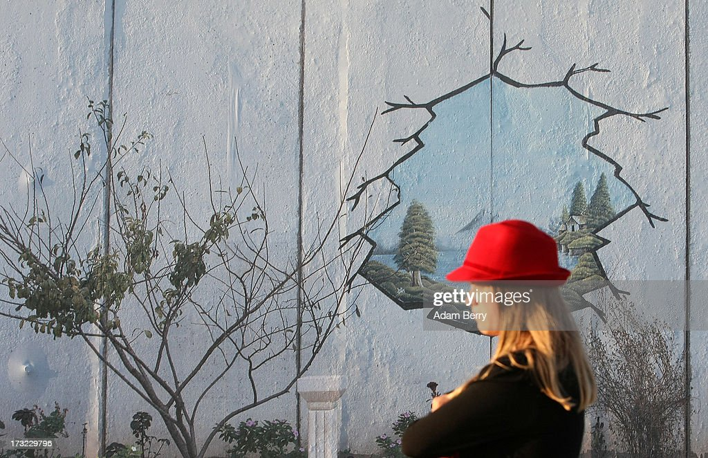 A visitor stands in front of a photo of a separation wall at Nazlat Issa in the West Bank, Occupied Palestinian Territories, in the 'Wall on Wall' exhibition at the East Side Gallery section of the former Berlin Wall on July 10, 2013 in Berlin, Germany. A series of photos shot since 2006 by photographer Kai Wiedenhoefer hanging on the Western, river Spree side of the Wall features large pictures of separation barriers in Baghdad, Korea, Cyprus, Mexico, Morocco, Israel, Belfast, and in the former East Germany itself. The opposite side of the stretch of the original Wall is known as East Side Gallery, a memorial to peace and freedom covered in murals questioning the legacy of the original Wall, and the subject of several demonstrations earlier in March this year when sections of it were threatened with removal to make way for a construction site for luxury apartment buildings, discussion of which is still ongoing with a decision expected to be reached in early August.