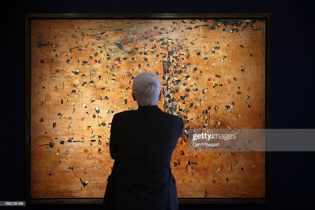 A visitor stands in front of a piece of work by Australian artist Fred Williams entitled 'You Yangs landscape 1', 1963 at Bonhams auction house on May 7, 2013 in London, England. The piece is expected to fetch between $1.5 - $2 Million AUS, (approximately £1-1.3M GBP) when it goes up for auction at an Australian Art sale at Bonhams in Sydney on June 26, 2013. The collection, which has never been seen before in public belongs to Neighbours producer Reg Grundy.