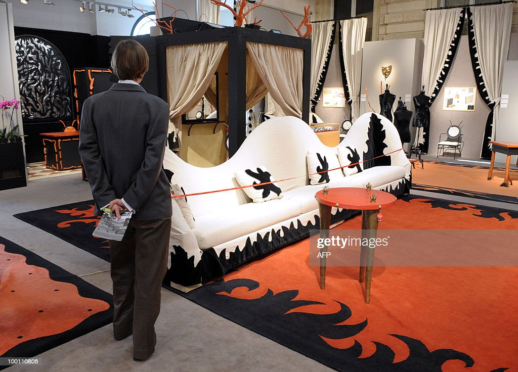 A visitor stands in front of one of the sofas designed by Elizabeth Garouste and Mattia Bonetti for French fashion house Christian Lacroix. The sofas are among about 100 lots exhibited at the auction house Sotheby's France in Paris on May 21, 2010 before a sale on May 26, 2010 organised at the initiative of Christian Lacroix Company. In 1987 Christian Lacroix hired furniture designers Garouste and Bonetti to create the complete bespoke interior of his fashion house located on the Parisian Faubourg Saint Honore. Apart from the salons, the team also designed the packaging, the writing paper, the logo.