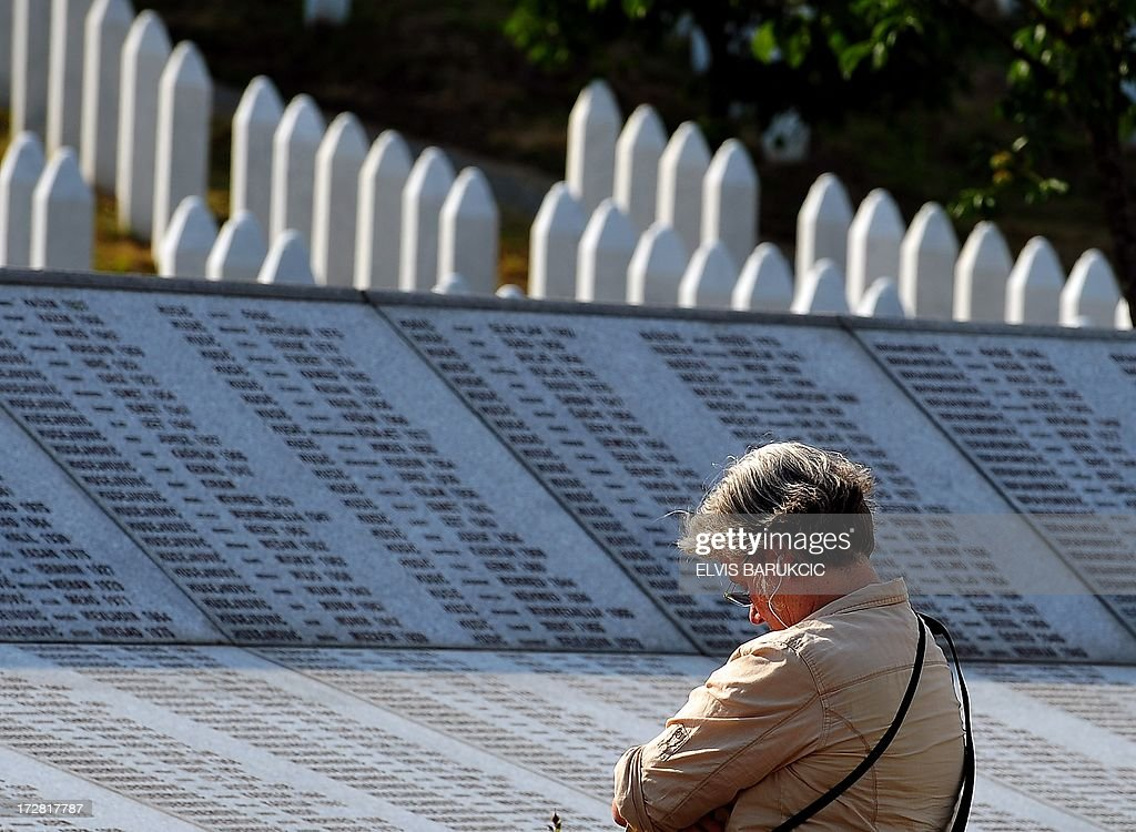 A visitor stands in front of the memorial wall at the Potocari Memorial cemetery near the Eastern-Bosnian town of Srebrenica, on July 4, 2013. The Potocari Memorial cemetery is undergoing preparations for another mass burial on July 11, when 408 newly identified bodies will be put to final rest. Bodies are identified as those belonging to Bosnian Muslim victims, of the offensive undertaken by Bosnian Serbs in July 1995 with the aim to occupy the earlier declared UN safe heaven area of Srebrenica and the surrounding villages. During the offensive more than 8000 Bosnian non-Serbs went missing to be found buried in mass graves, years after the war ended.