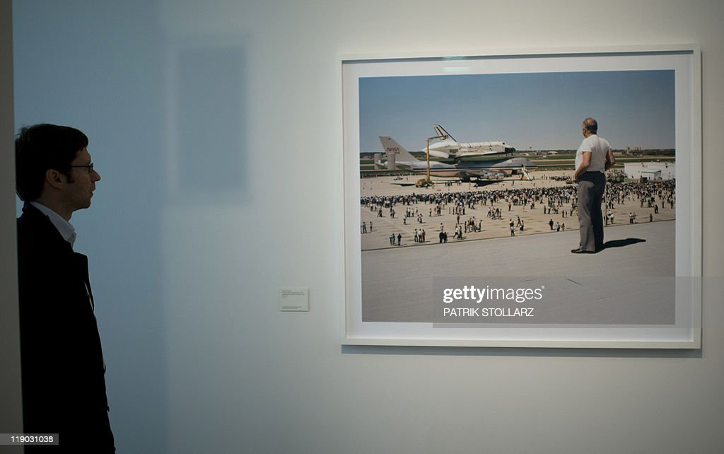 A visitor stands in front of the photo 'The space shuttle Colombia lands on Air Force Base Kelly Lackland San Atonio 1979' from American photographer Joel Sternberg during a preview of the exhibition 'Color Photographs Since 1970 'at the Museum Folkwang in Essen, western Germany, on July 14, 2011. The Museum Folkwang is dedicating a first European retrospective to the American photographer Joel Sternfeld (*1944, New York) from 16 July 2011,to 23 October with around 130 works from over three decades.