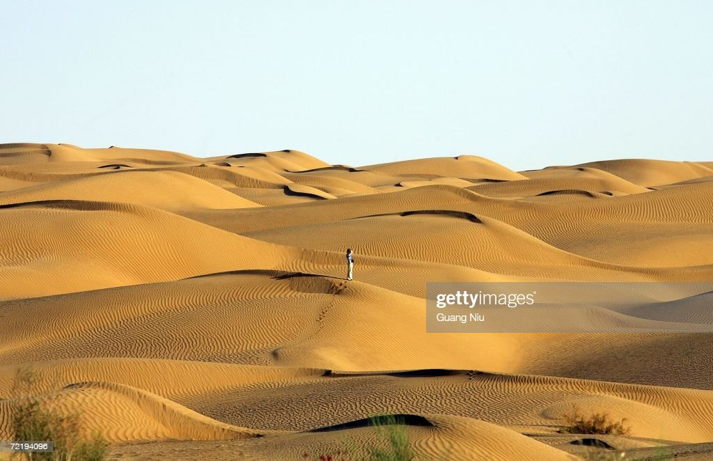 A visitor stands in Taklimakan Desert on October 12 2006 near Yutian county Xinjiang Uygur Autonomous Region China The Taklimakan desert is one of...