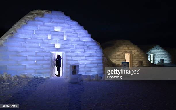 A visitor stands in the doorway to an illuminated room made from snow and ice at night at the Royce' Ice Hills Hotel in Tobetsu Hokkaido Japan on...