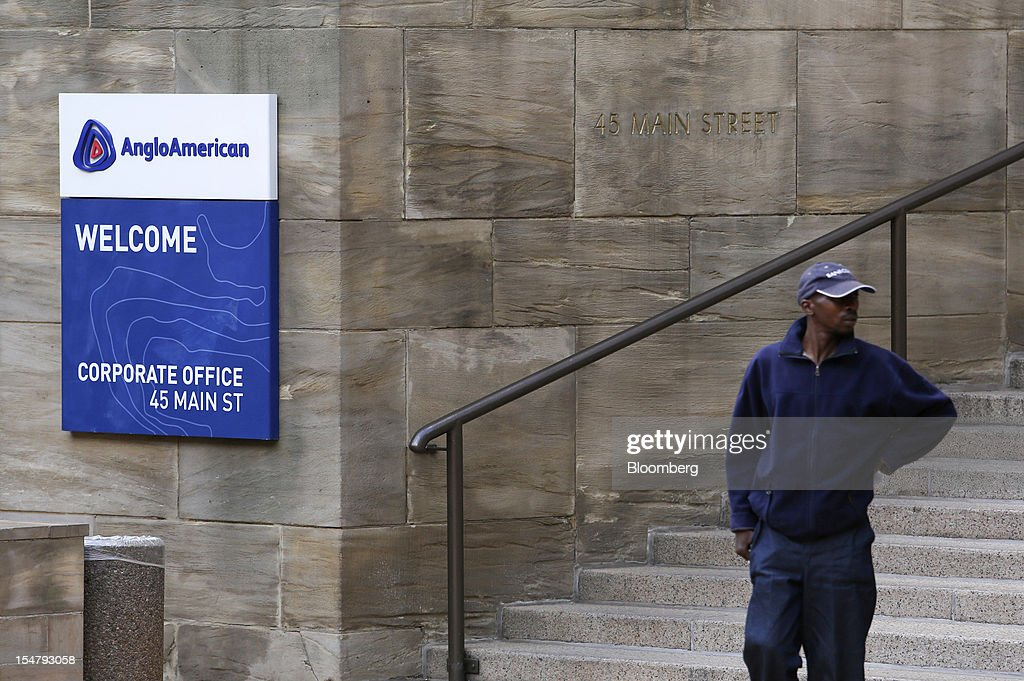 A visitor stands near a company sign outside the offices of Anglo American Plc in the Marshalltown district of Johannesburg, South Africa, on Friday, Oct. 26, 2012. Anglo American Plc Chief Executive Officer Cynthia Carroll , the first woman, external hire and non-South African to hold the job, will quit after Anglo lost $14 billion in value in the more than five years she was in charge. Photographer: Chris Ratcliffe/Bloomberg via Getty Images