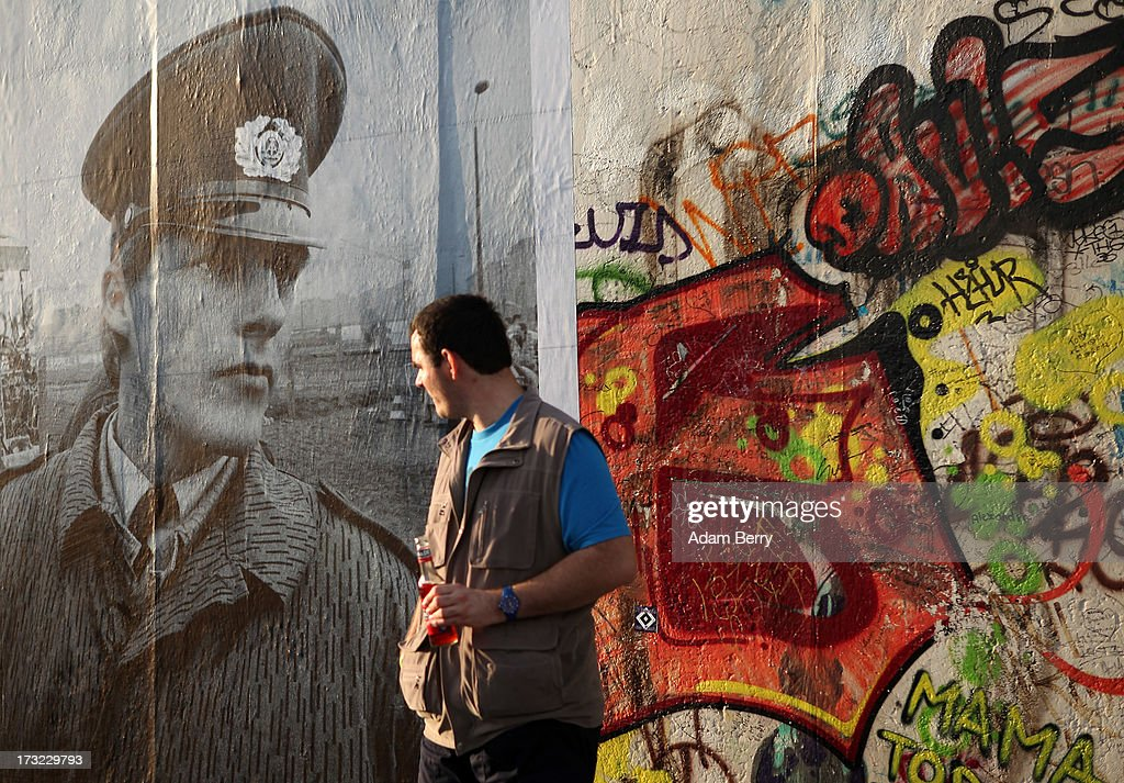 A visitor stands near a photo of a German Democratic Republic (GDR) border guard at the former border between East and West Germany, hanging as part of the 'Wall on Wall' exhibition at the East Side Gallery section of the former Berlin Wall on July 10, 2013 in Berlin, Germany. A series of photos shot since 2006 by photographer Kai Wiedenhoefer hanging on the Western, river Spree side of the Wall features large pictures of separation barriers in Baghdad, Korea, Cyprus, Mexico, Morocco, Israel, Belfast, and in the former East Germany itself. The opposite side of the stretch of the original Wall is known as East Side Gallery, a memorial to peace and freedom covered in murals questioning the legacy of the original Wall, and the subject of several demonstrations earlier in March this year when sections of it were threatened with removal to make way for a construction site for luxury apartment buildings, discussion of which is still ongoing with a decision expected to be reached in early August.