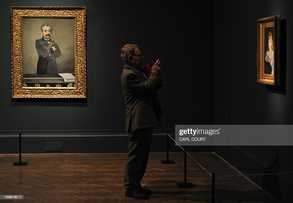 A visitor stands next to a painting by French artist Edouard Manet entitled 'Portrait of Georges Clemenceau' (L) as he takes a photograph of a painting titled 'Portrait of Lise Campineanu' at the Royal Academy of Arts in central London on January 22, 2013. Forming part of the 'Manet: Portraying Life' exhibition, it is due to be displayed from January 26 to April 14.