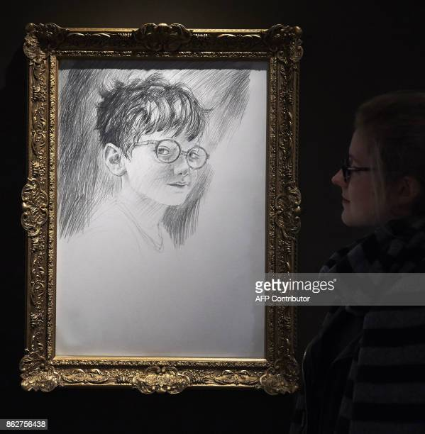 A visitor stands next to a sketch titled 'The Boy who Lived' during a preview of 'Harry Potter A History of Magic' exhibition at the British Library...