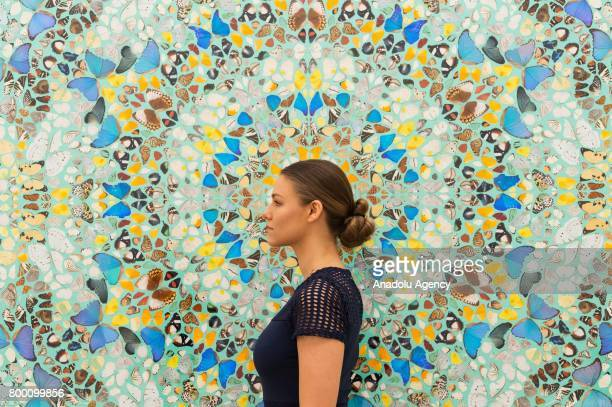 A visitor stands next to the artwork titled Contemplation by artist Damien Hirst with a sale estimate of £700000£900000 in London United Kingdom on...