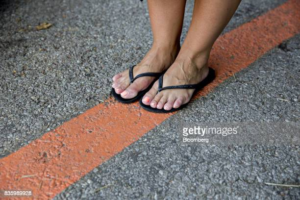 A visitor stands on a painted line indicating the anticipated center line for the upcoming total solar eclipse in Makanda Illinois US on Saturday Aug...