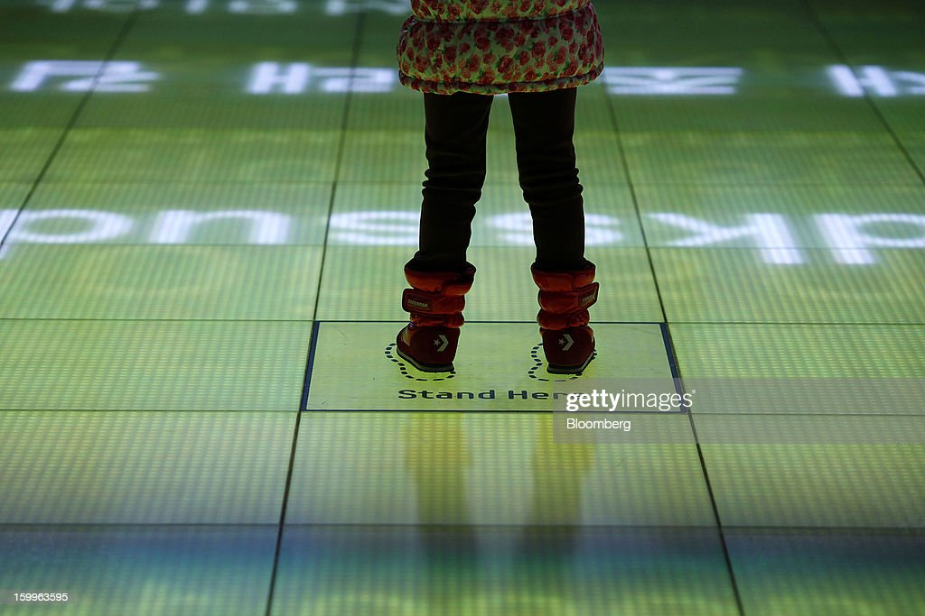 A visitor stands on the floor of the d'light stage as she tries Samsung Electronics Co's Augmented Reality technology at the Samsung Electronics Co. Samsung d'light showroom and store in Seoul, South Korea, on Wednesday, Jan. 23, 2013. Samsung, in a preliminary statement of results on Jan. 8, reported an 89 percent jump in profit in the three months ended in December, boosted by its Galaxy line of smartphones. Photographer: Woohae Cho/Bloomberg via Getty Images