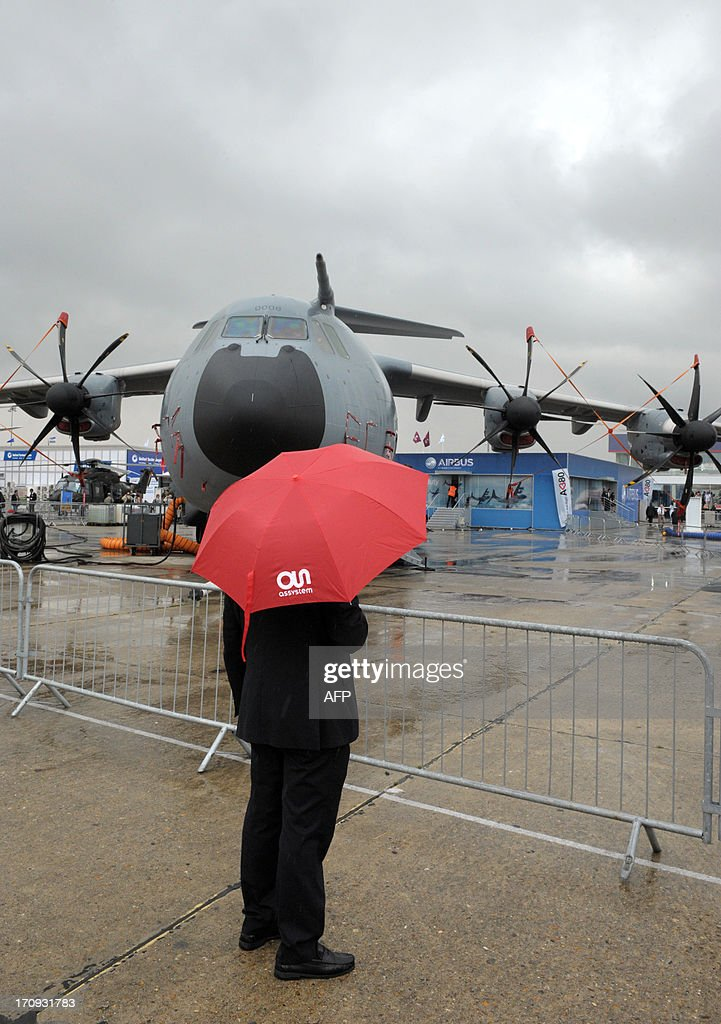 A visitor stands under an umbrella in front of the Airbus A400 M at Le Bourget airport, near Paris on June 20, 2013 during the 50th International Paris Air show.