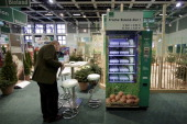 A visitor stays beside a selfservice machines for eggs at the Gruene Woche agricultural trade fair on January 17 2014 in Berlin Germany The Gruene...