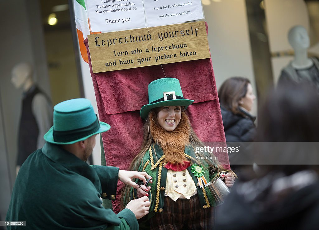 A visitor steps into a mock Leprechaun outfit and poses for a photograph in Grafton Street in Dublin, Ireland, on Saturday, March 16, 2013. Ireland's renewed competiveness makes it a beacon for the U.S. companies such as EBay, Google Inc. and Facebook Inc., which have expanded their operations in the country over the past two years. Photographer: Simon Dawson/Bloomberg via Getty Images