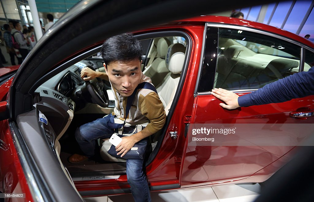 A visitor steps out from the driver's seat of a Buick vehicle displayed at the Shanghai General Motors Co. booth, the joint venture between General Motors Co. and SAIC Motor Corp., at the Wuhan Motor Show 2013 in Wuhan, China, on Saturday, Oct. 19, 2013. The show will be held through Oct. 23. Photographer: Tomohiro Ohsumi/Bloomberg via Getty Images