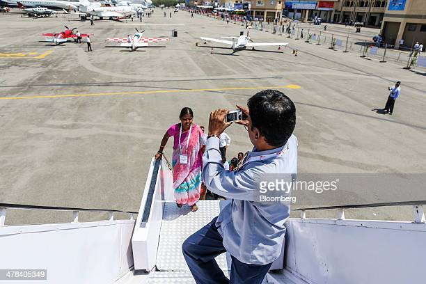 A visitor stops to take a photograph while boarding a Boeing Co 787 Dreamliner aircraft operated by Air India Ltd on display during the India...