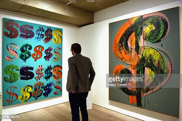 A visitor studies 'Dollar Signs' by Andy Warhol which has an estimated value of £4565 million and is going on show at Sotheby's on June 8 2015 in...
