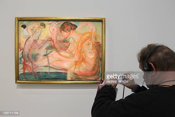 A visitor take a photograph of the painting 'Femmes au bain' at the Centre Pompidou modern art museum also known as the 'Centre Beaubourg' during the...