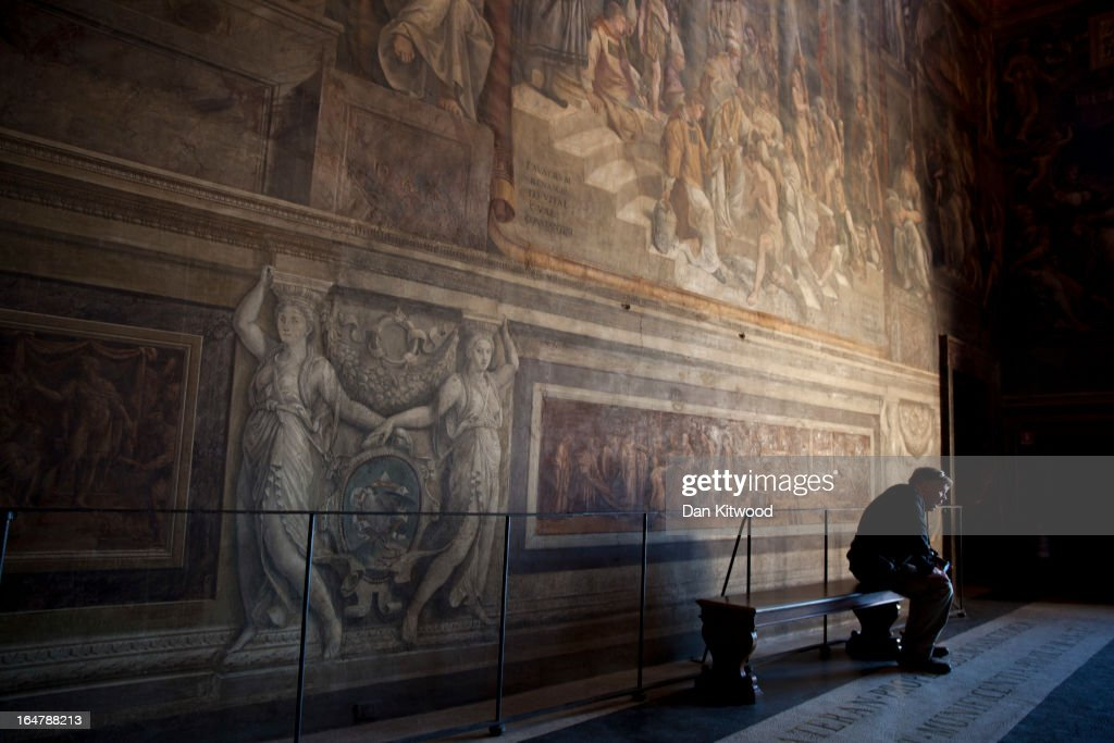 A visitor takes a break in the Vatican Museum's Raphael Room's on March 21 2013 in Rome Italy