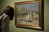 A visitor takes a closer look at Caillebotte's 'The Market Place' during the press preview of the exhibition 'Caillebotte pintor y jardinero' at the...