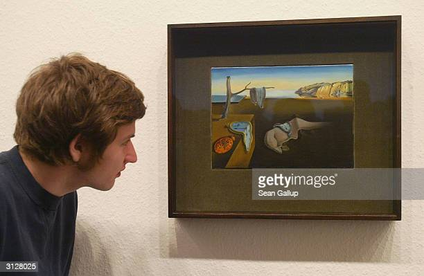 A visitor takes a look at Salvador Dali's 'The Persistence of Memory' at the MoMA exhibit on March 24 2004 in Berlin Germany The exhibit which opened...