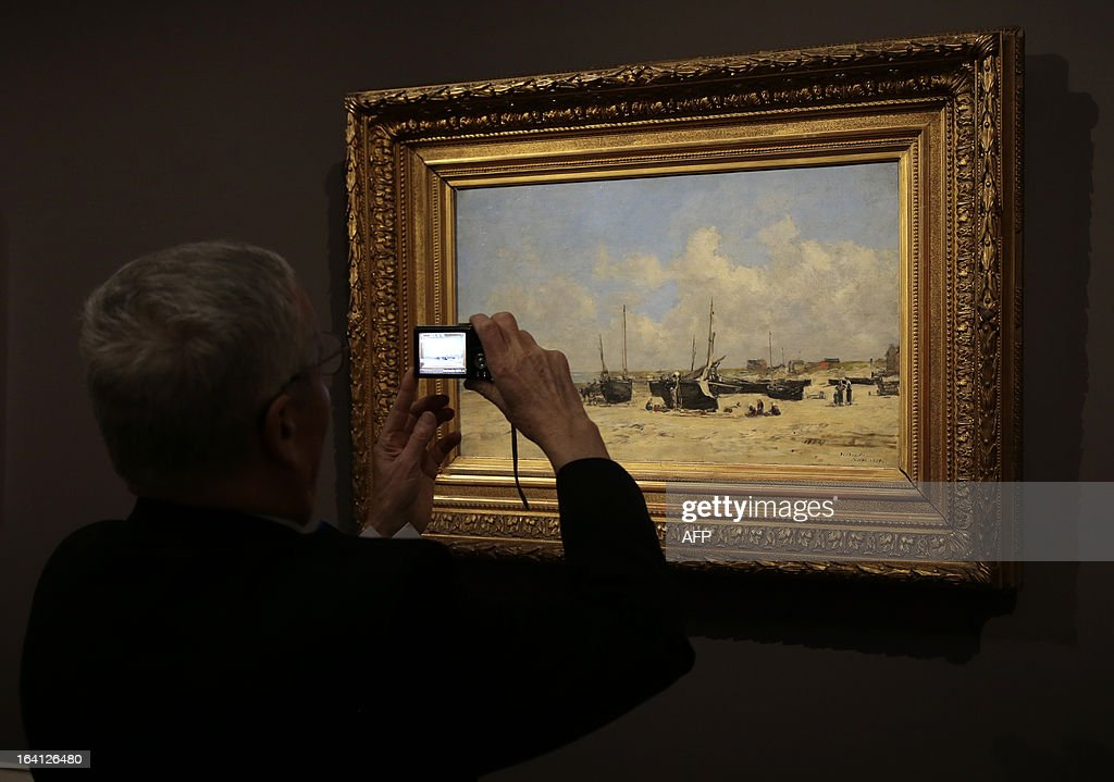 A visitor takes a mobile phone picture of the painting 'la plage de Berck' on March 20, 2013 at the Jacquemart-Andre museum during the inaugural visit to the French painter Eugene Boudin's (1824 - 1898) exhibition running from March 22 to July 22, 2013. AFP PHOTO/JACQUES DEMARTHON