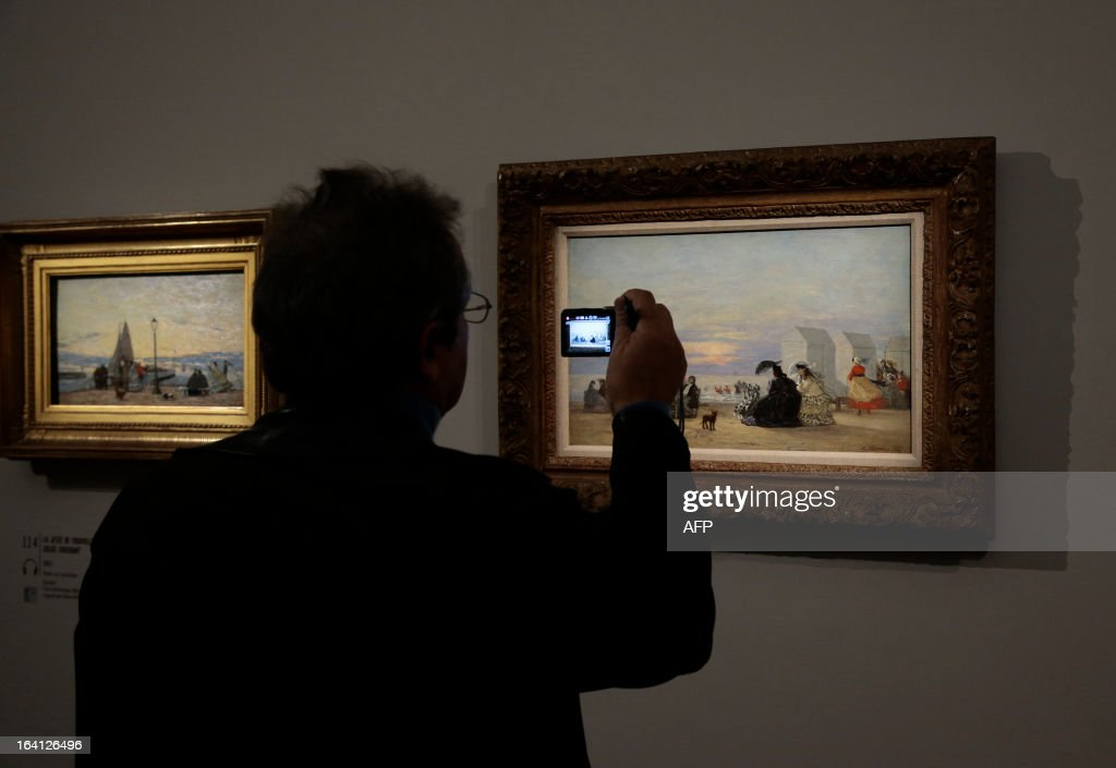 A visitor takes a mobile phone picture of the paintings, 'la jetee de Trouville, soleil couchant' (L) and 'plage, au soir' (R), on March 20, 2013 at the Jacquemart-Andre museum during the inaugural visit to the French painter Eugene Boudin's (1824 - 1898) exhibition running from March 22 to July 22, 2013. AFP PHOTO/JACQUES DEMARTHON