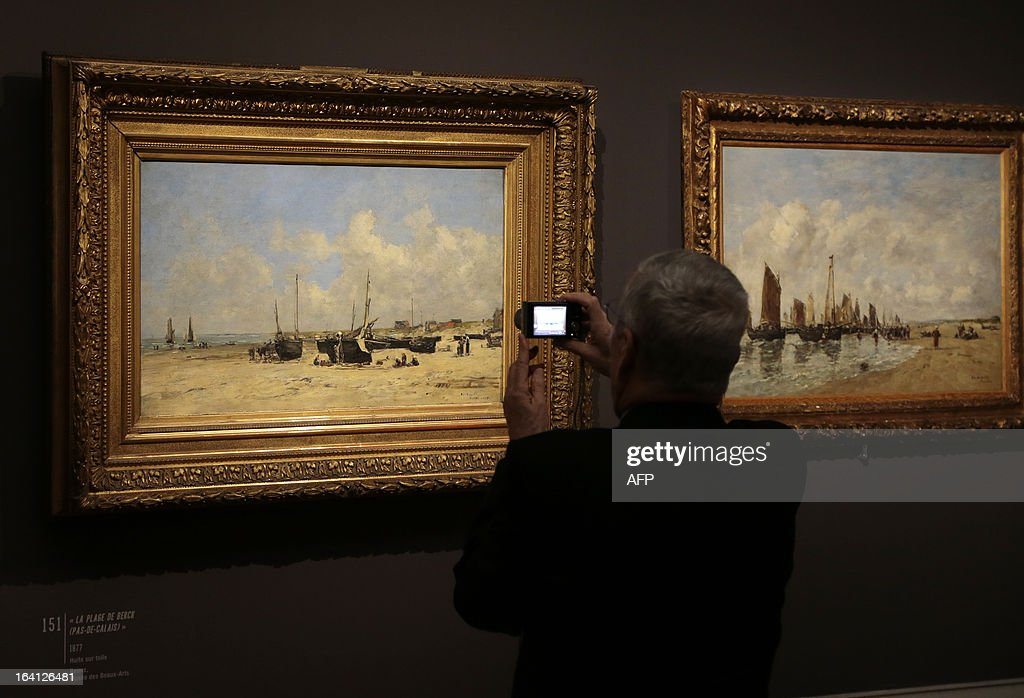 A visitor takes a mobile phone picture of the paintings, 'la plage de Berck ' (L) and 'la plage de Berck, maree haute' on March 20, 2013 at the Jacquemart-Andre museum during the inaugural visit to the French painter Eugene Boudin's (1824 - 1898) exhibition running from March 22 to July 22, 2013.