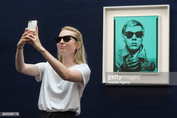 A visitor takes a mobile phone selfie with a self portrait silk screen print of artist Andy Warhol with a sale estimate of £5000£7000 in London...