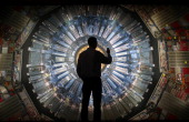 A visitor takes a phone photograph of a large back lit image of the Large Hadron Collider at the Science Museum's 'Collider' exhibition on November...