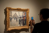 A visitor takes a photo at Caillebotte's 'Sketch for Paris Street Rainy Day' during the press preview of the exhibition 'Caillebotte pintor y...