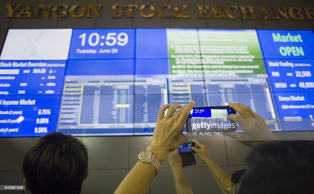 A visitor takes a photo of a large video screen displaying stock prices at the Yangon Stock Exchange in Yangon on June 28, 2016. / AFP / YE