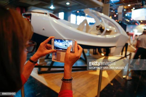 A visitor takes a photo of a prototype of the Sea Bubbles Flying River Taxi during the Viva Technology event dedicated to startup development...