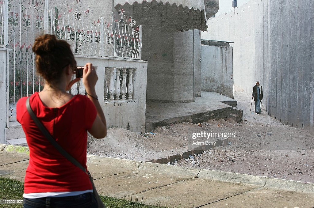 A visitor takes a photo of a separation wall in Nazlat Issa, in the West Bank, Occupied Palestinian Territories, as it hangs as part of the 'Wall on Wall' exhibition at the East Side Gallery section of the former Berlin Wall on July 10, 2013 in Berlin, Germany. A series of photos shot since 2006 by photographer Kai Wiedenhoefer hanging on the Western, river Spree side of the Wall features large pictures of separation barriers in Baghdad, Korea, Cyprus, Mexico, Morocco, Israel, Belfast, and in the former East Germany itself. The opposite side of the stretch of the original Wall is known as East Side Gallery, a memorial to peace and freedom covered in murals questioning the legacy of the original Wall, and the subject of several demonstrations earlier in March this year when a section of it were threatened with removal to make way for a construction site for luxury apartment buildings, discussion of which is still ongoing with a decision expected to be reached in early August.
