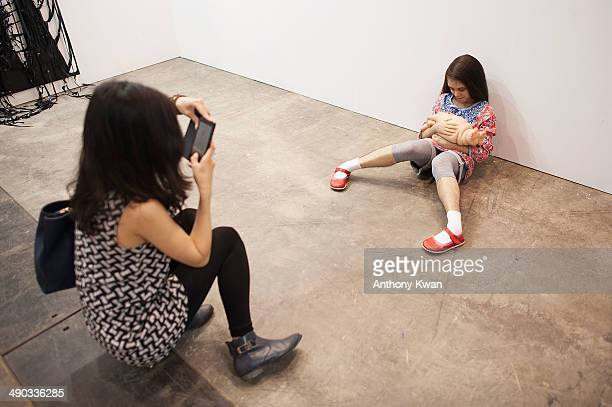 Visitor takes a photo of an art installation entitled 'The Comforter' by Patricia Piccinini at Art Basel Hong Kong on May 14 2014 at the Hong Kong...