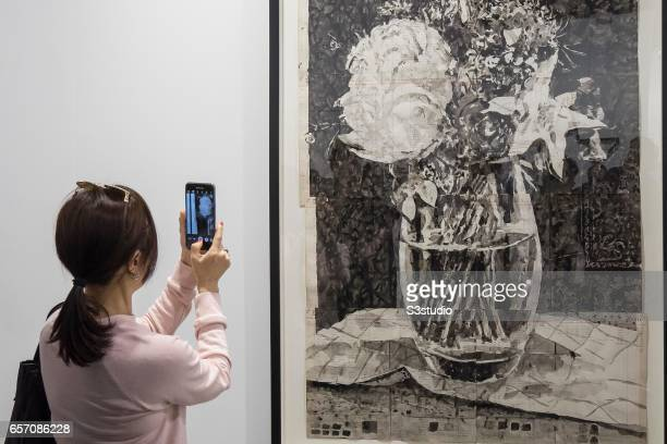 A visitor takes a photo of artist William Kentridge's 'Untitled 2016' during Art Basel Hong Kong 2017 at Hong Kong Convention and Exhibition Centre...