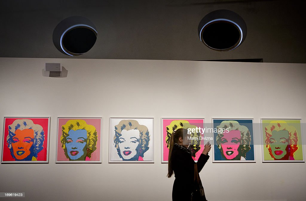 A visitor takes a photo of collection by Andy Warhol during a press preview of the 'Marilyn' exhibition at Prague Castle on May 29, 2013 in Prague, Czech Republic. The exhibition was created by the Museo Salvatore Ferragamo in Florence, in 2012. Marilyn Monroe loved and owned many pairs of shoes made by Ferragamo. The Marilyn exhibition, which commemorates the 50th anniversary of her death, runs at the Riding School until September 20, 2013. The exhibition will present 30 pairs of shoes and over 50 outfits and other accessories from Marylin's personal, public and movie wardrobe and also historical movie clips, magazine covers and Marilyn's original writings.