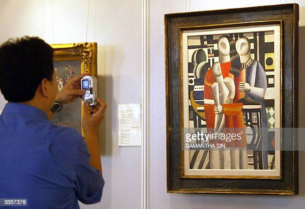 A visitor takes a photo of 'Les deux femmes a l'enfant' by French Cubist painter Fernand Leger estimated at some 23 million USD the most valuable...