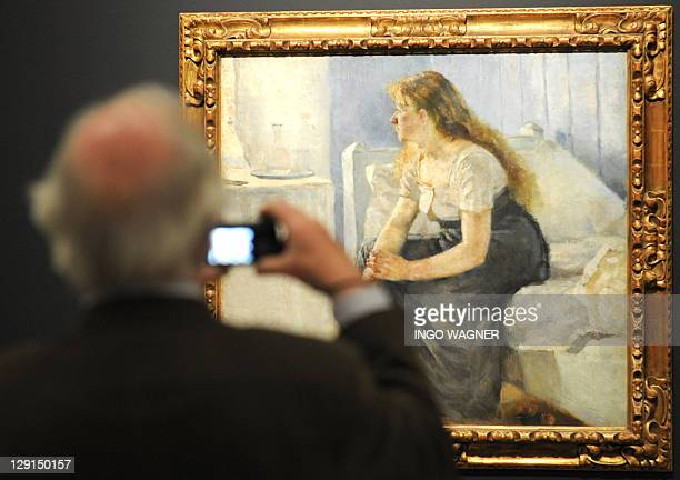 A visitor takes a photo of the painting 'Morgen1884' by Norwegian artist Edvard Munch on display at the 'Kunsthalle Bremen' gallery in the northern...