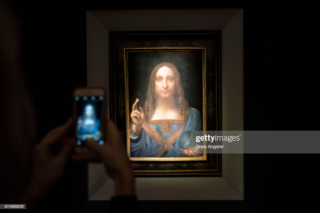 A visitor takes a photo of the painting 'Salvator Mundi' by Leonardo da Vinci at Christie's New York Auction House, November 15, 2017 in New York City. The coveted painting is set to be auctioned off on Wednesday night and has been guaranteed to sell for over $100 million.