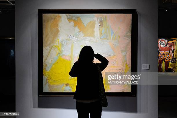 A visitor takes a photo of Willem de Kooning's 'Pastorale' with JeanMichel Basquiat's 'Sugar Ray Robinson' in the background at 'The Loaded Brush'...